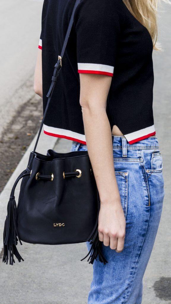 Clos Up von Strickoberteil, Jeans und Tasche