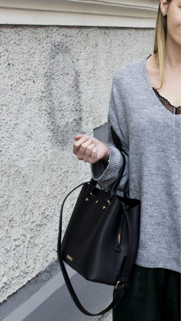 Das Bild zeigt einen Ausschnitt von einer Frau mit grauem Pullover und grünem Slip Dress darunter. Sie trägt eine schwarze Tasche