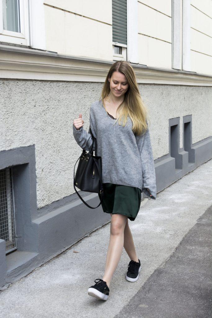 Auf dem Bild ist eine Frau in einem grauen Pullover, grünem Slip Dress darunter und Sneakers zu sehen