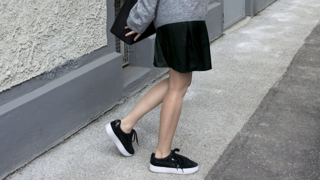 Das Bild zeigt einen Ausschnitt mit schwarzen Sneakers von Puma.