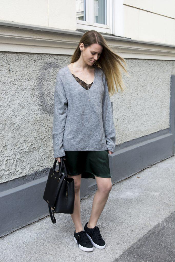 Das Bild zeigt eine Frau im grünen Slip Dress mit grauem Pullover darüber und einer schwarzen Tasche.