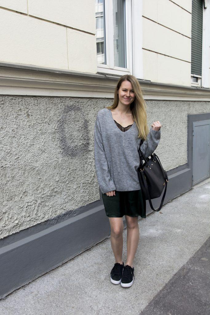 Das Bild zeigt eine Frau im grünen Slip Dress mit grauem Pullover darüber.