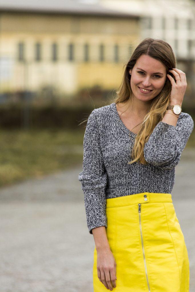 Das Bild zeigt eine Frau die in die Kamera blickt und lächelt. Sie trägt eine kurzen gelben Rock und einen grauen Pullover.