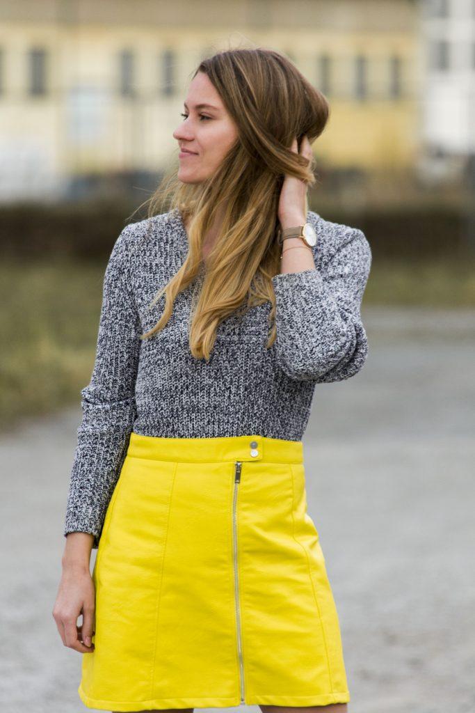 Das Bild zeigt eine Frau in einem gelben Kunstlederrock.