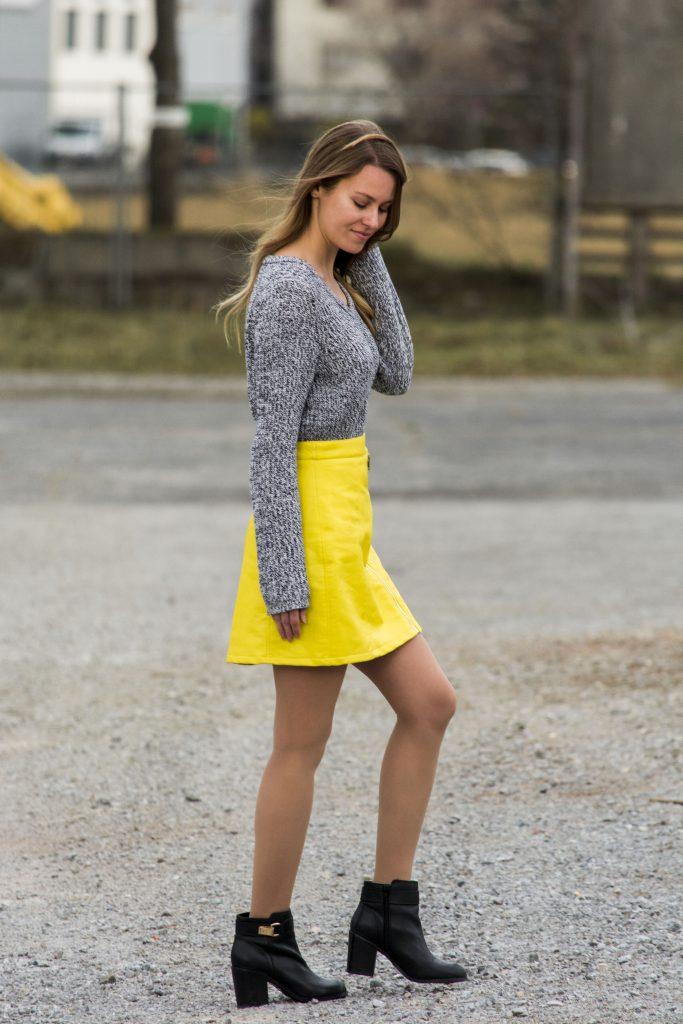 DasBild zeigte eine Frau in einem gelben Rock, einem grauen Pullover und schwarzen Stiefletten.