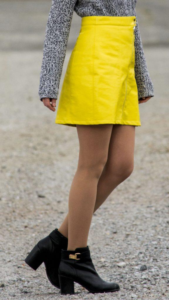 Das Bild zeigt einen Bein-Ausschnitt von dem Outfit mit gelben Rock.